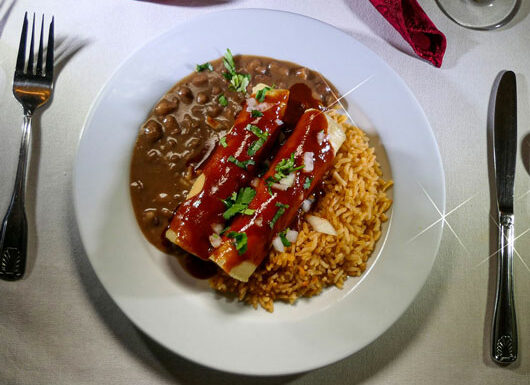 Cheese Enchiladas – enchilada made with corn tortillas and a savory sauce, served with Mexican rice and beans